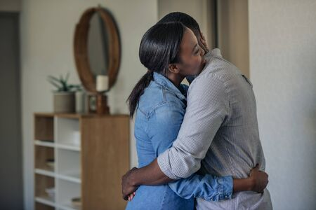 Affectionate young African American couple hugging each other at home
