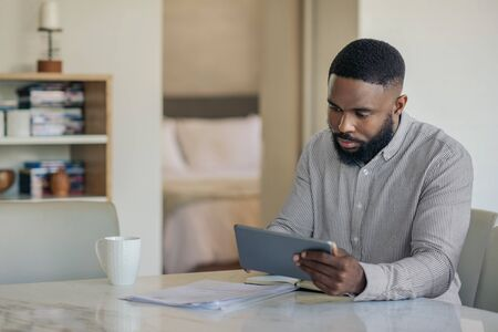 African American man doing his online banking with a tablet Zdjęcie Seryjne