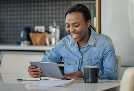 Laughing African American woman using a digital tablet at home