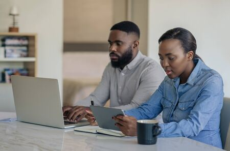Young African American couple doing online banking together at home