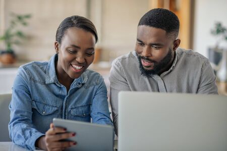 Smiling young African American couple working online together at home
