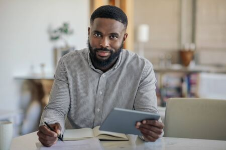 Smiling African American man using a digital tablet at home