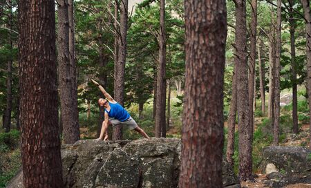 Man doing an extending side angle pose in the woods