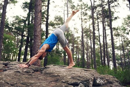 Man doing the downward facing dog pose in a forest