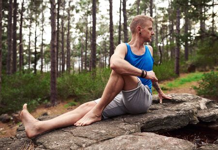 Man doing the seated spinal twist pose in a forest