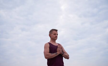Man meditating during yoga practice against a sky at dusk
