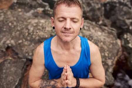 Man sitting with eyes closed on a rock and meditating Stockfoto