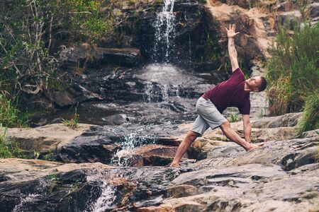 Fit man doing the triangle pose by a waterfall