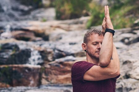 Man doing the eagle pose on rocks by a waterfall Stockfoto