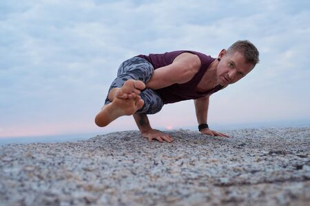 Fit man doing the eight angle pose on a rock