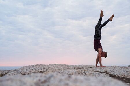 Man doing a hand stand while practicing yoga at dusk Stockfoto