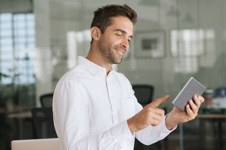 Smiling businessman standing in an office using a digital tablet