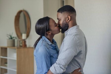 Romantic young African American couple kissing at home Zdjęcie Seryjne