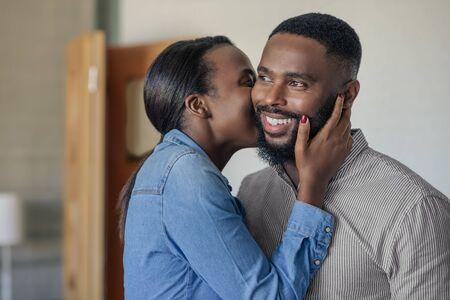 Sonriente hombre afroamericano recibiendo un beso de su esposa