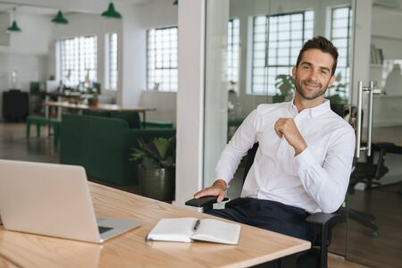 Smiling young businessman sitting at his desk in an office