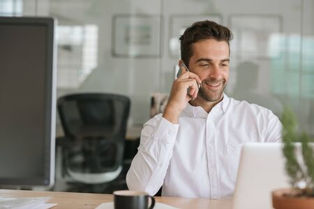 Smiling businessman talking on a cellphone at his office desk