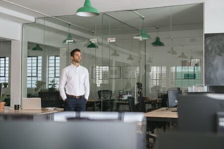 Young businessman standing in an office looking deep in thought