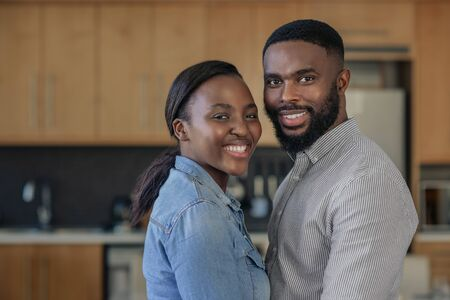 Affectionate young African American couple standing close together at home