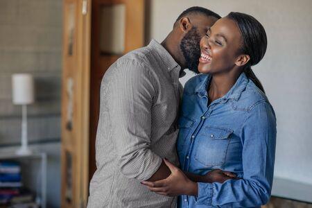 Afectuoso marido afroamericano besando a su esposa en la mejilla
