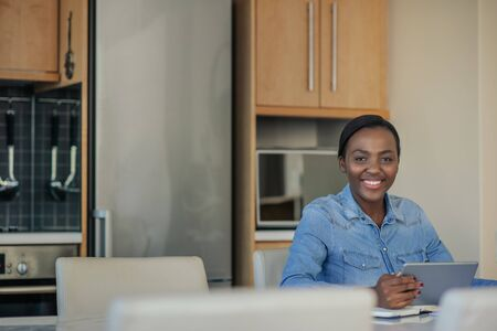 Smiling African American woman using a tablet in her kitchen