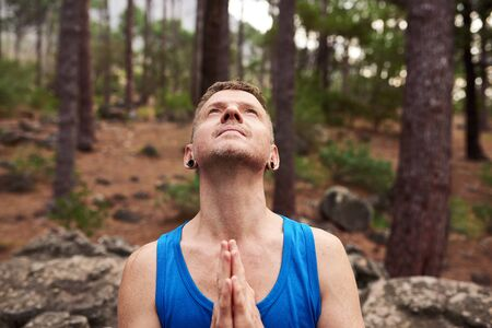 Man looking to the sky and praying in a forest