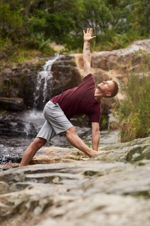 Man doing the triangle pose on rocks by a waterfall Stockfoto