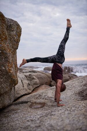 Man doing a hand stand by rocks while practicing yoga Stockfoto