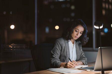 Jeune femme d'affaires travaillant dans son bureau la nuit