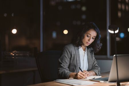 Young businesswoman working in her office at night