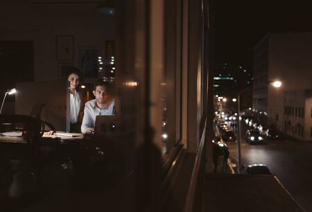Businesspeople working inside of an office late in the evening
