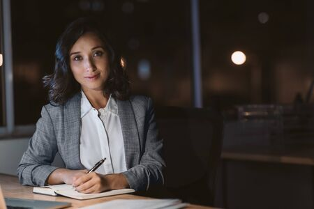 Young businesswoman smiling while working in her office at night