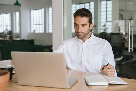 Young businessman writing down notes while working on a laptop