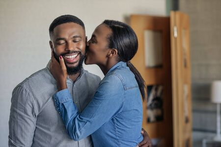 Loving African American wife kissing her husband on the cheek Foto de archivo