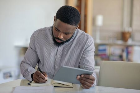 Young African American man using a digital tablet at home