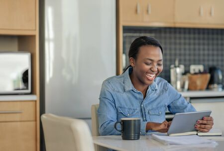 Laughing African American woman using a tablet in her kitchen 写真素材