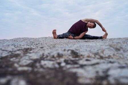 Man doing the revolved head to knee pose at dusk Stockfoto