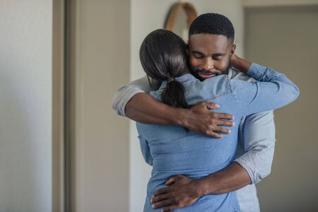 Affectionate young African American man hugging his wife at home