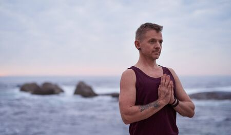 Man meditating during yoga practice by the ocean at dusk