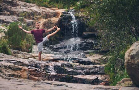 Man doing the extended standing hand to toe pose outdoors