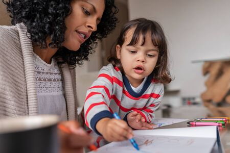 Caring mother and her adorable little girl coloring at home