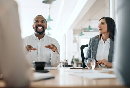Smiling African American businessman talking with colleagues during a meeting Stock Photo