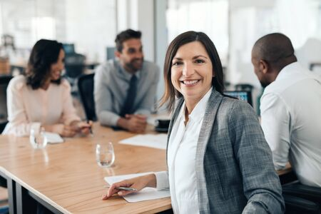 Smiling businesswoman sitting with colleagues during an office meeting