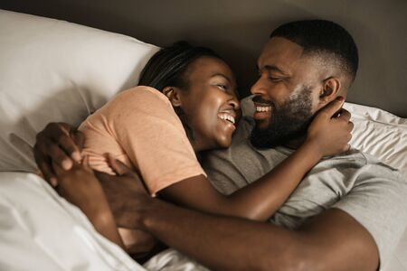 Young African American couple laughing together in bed Banque d'images - 130068397