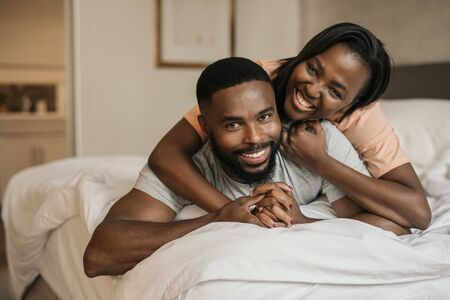Smiling young African American couple playing in bed together Stockfoto
