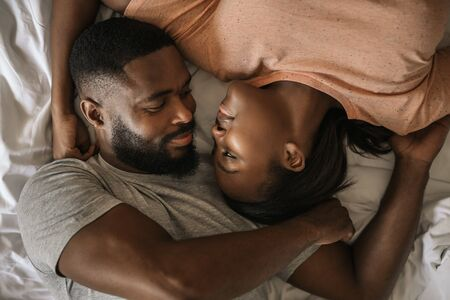 Loving African American couple looking at each other in bed Banque d'images - 130068404