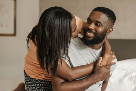 Affectionate African American couple sitting on their bed wearing pajamas