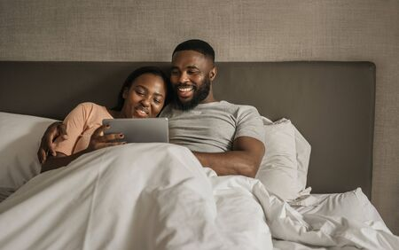 Smiling young African American couple using a tablet in bed