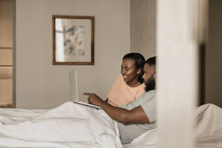 Smiling young African American couple using a laptop in bed