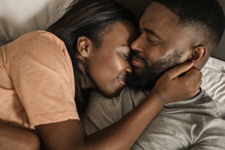 Smiling young African American couple hugging each other in bed Banque d'images - 130068356