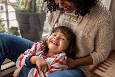 Uśmiechnięta mama i urocza córka bawią się razem w domu